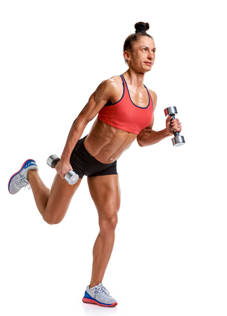 a young and very fit woman with dumbbells in studio on grey background Stock Photo