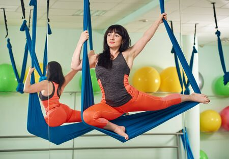 hang body: middle-aged woman in fly yoga exercise