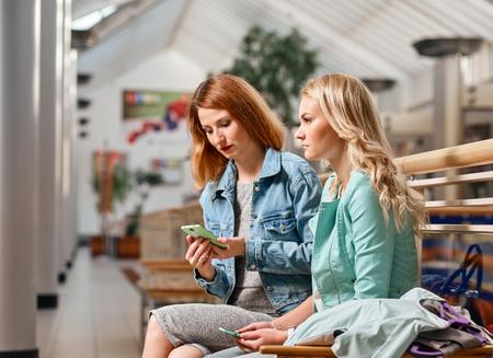 compras compulsivas: dos mujeres con teléfonos inteligentes y bolsas de compras