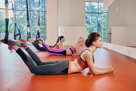 three fitness women at gym relax