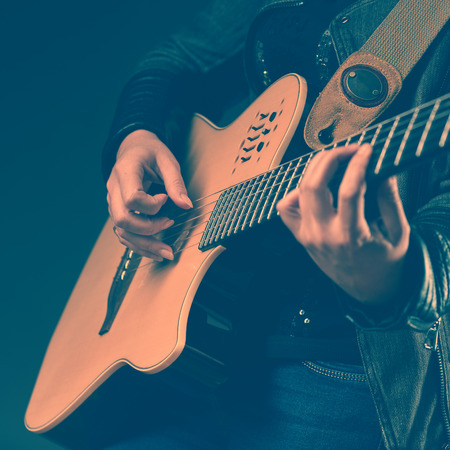 instrumentalist: Woman playing on the guitar