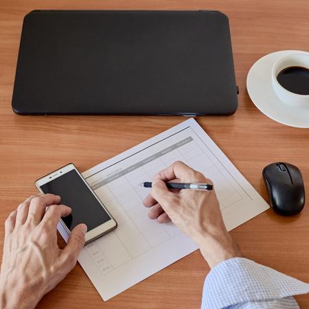 Businessman filling timesheet