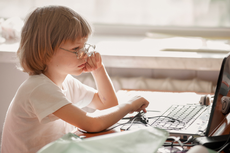 Concentrated little boy wearing glasses using computer