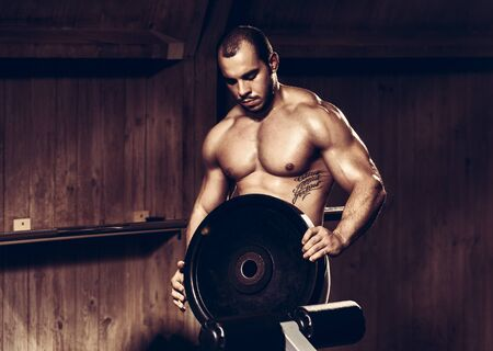 Athlete man with weightlifting plate Stock Photo