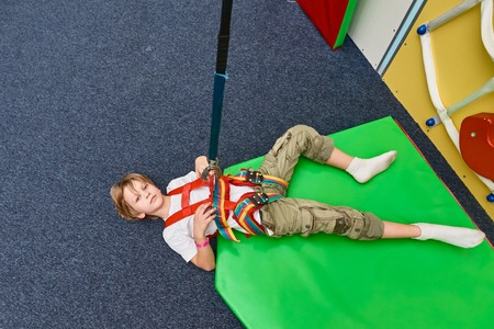 Young happy boy resting after climbing in adventure park