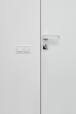 Closeup of white door in modern room with light switch
