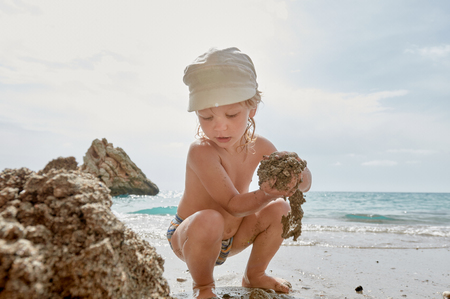 Cute young boy playing with sand on the tropical beach Standard-Bild
