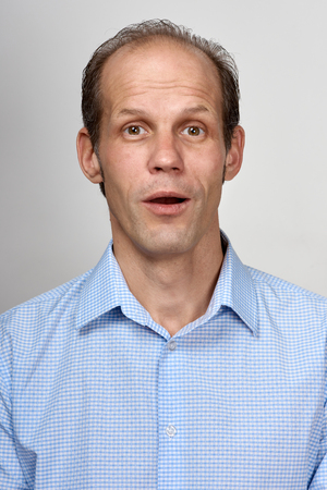 Portrait of surprised young business man on light gray background