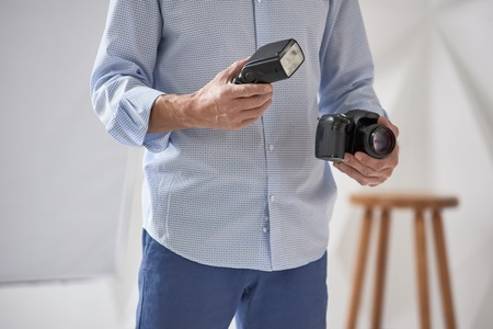 Closeup of young man holding digital camera with synchronizer and flash in studio, focus is on hand with flash