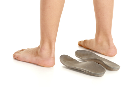 Orthopedic insoles and little boy legs on white background