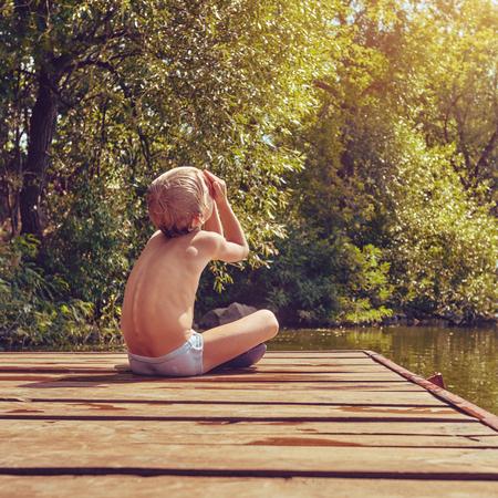 Resting boy near river