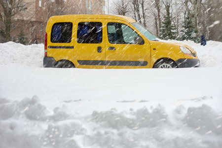 Yellow car on snowfall 스톡 콘텐츠