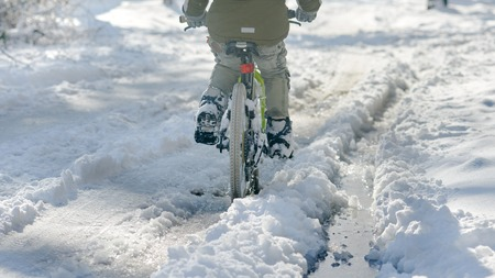 Closeup of young boy with bicycle on snow cover road Banco de Imagens