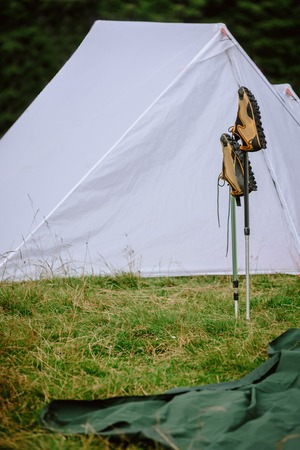 Closeup of shoes on trekking sticks against tourist tent in mountains
