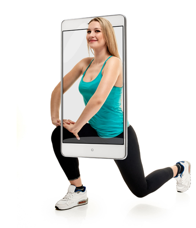 Attractive smiling sporty woman squatting on white background, concept virtual reality of the smartphone. going out of the device Banco de Imagens