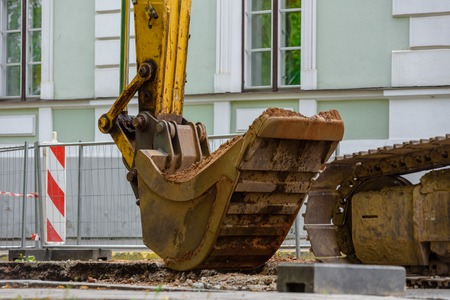 Closeup of excavator working on repairing road on city street Stock Photo