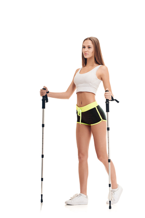 Slim beautiful woman doing nordic walking exercise