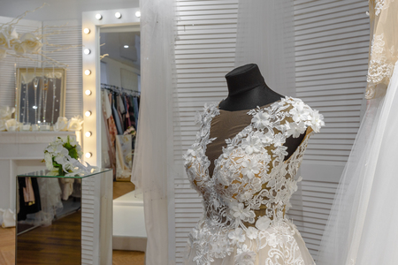 Beautiful bridal dress on mannequin in modern wedding showroom