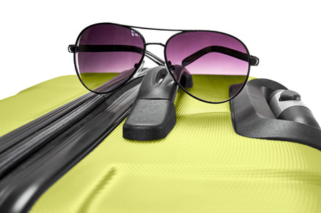 Set of travel accessories: stylish glasses lying on light green suitcase Stock Photo