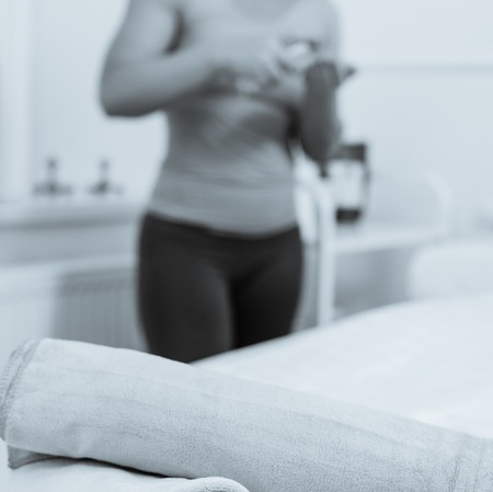 Female masseur preparing her hands with oil, focus on stacked towels. photo converted in black and white with a blue tint