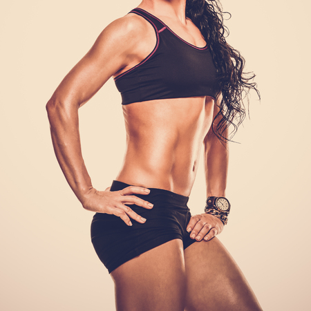 Closeup photo of sporty woman with perfect muscular body