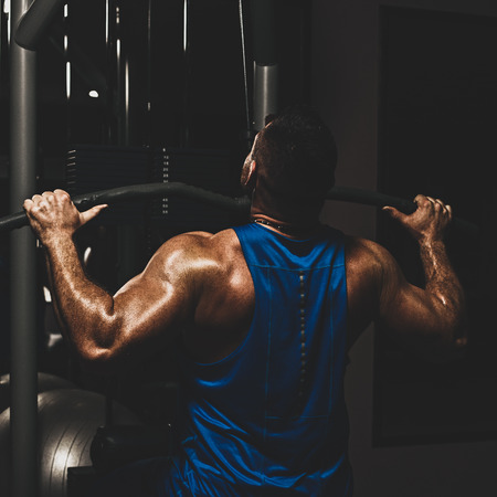 Strong male bodybuilder doing exercise for back with lat pulldown machine in gym, with color imitating social network filter Stock Photo