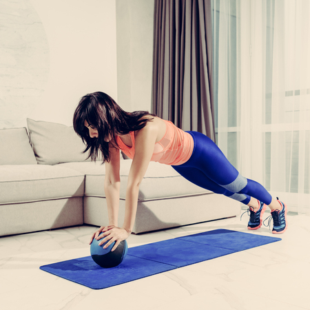 Slim healthy woman doing plank exercise with ball at home, image with warm vintage toning
