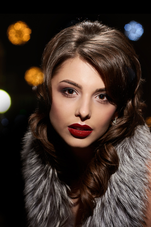 Retro portrait of young beautiful woman with fur collar, background with different highlights 写真素材