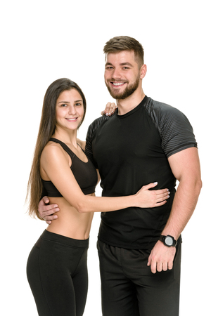 Young beautiful couple in black sportswear posing on white background