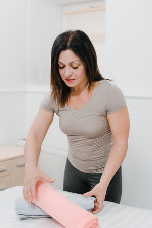 Young female masseur preparing towels for massage procedure