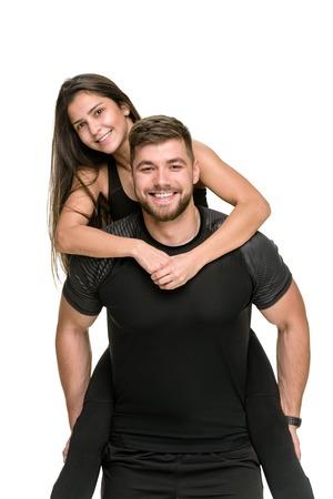 Smiling happy athlete piggybacking his laughing girlfriend Stock Photo
