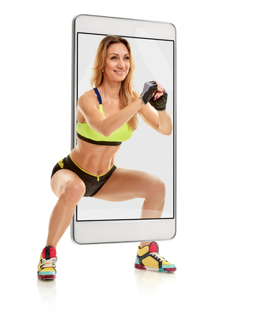 Portrait of young fit sporty woman doing squat, concept virtual reality of the smartphone. going out of the device