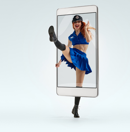 Beautiful smiling dancer dressed as policewoman raising leg, concept virtual reality of the smartphone. going out of the device