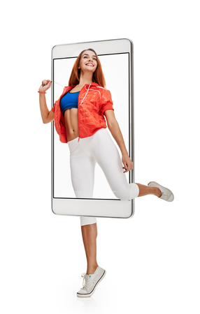 Young sportswoman doing warming-up exercises before training, concept virtual reality of the smartphone. going out of the device