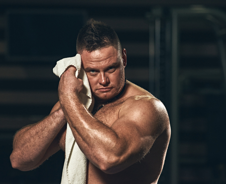 Strong athletic handsome man wiping body after training