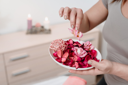 Closeup of female masseur preparing for spa procedure with red rose petals
