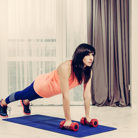 Beautiful slim sporty woman doing plank exercise with dumbbells, image with warm vintage toning Фото со стока