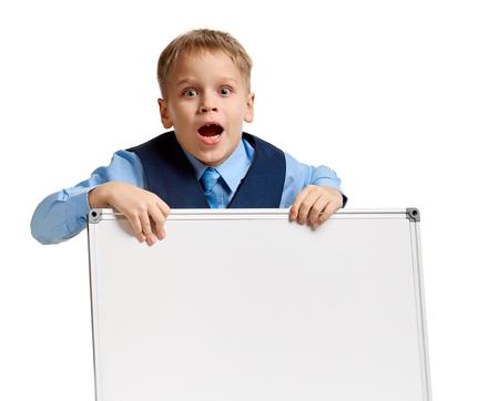 Portrait of little surprised schoolboy in uniform holding whiteboard