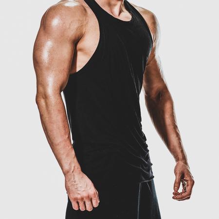 Teil des jungen lächelnden fitten Bodybuilders, der seinen trainierten Körper zeigt Standard-Bild