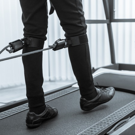 Closeup photo of man walking on treadmill with electrodes on his legs black white image with a blue toning