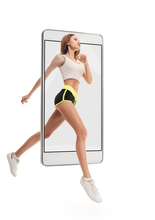 Portrait of young sporty energetic healthy woman running, concept virtual reality of the smartphone. going out of the device