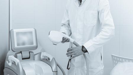 Male beautician using modern machine for vitiligo treatment black white image with a blue toning