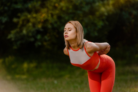 Attractive young sporty woman exercising in park at morning Stok Fotoğraf
