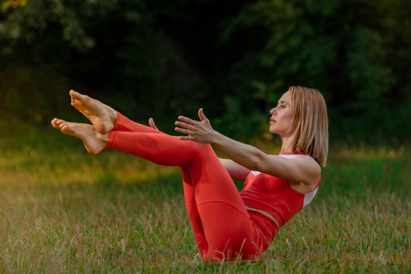Healthy fit woman doing yoga exercise on green lawn