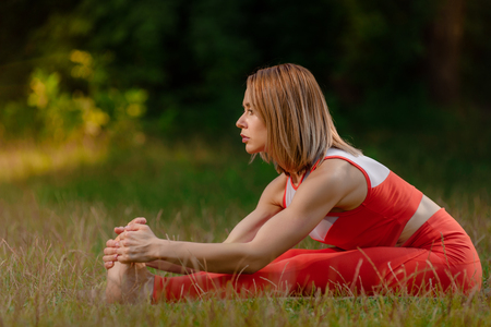 Fit young woman stretching her legs while sitting on grass 写真素材