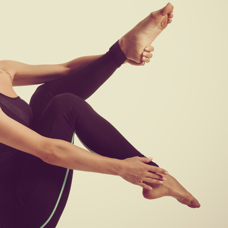Young healthy woman in black sportswear doing pilates exercise. Part of body