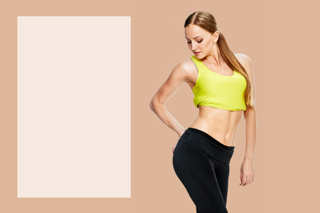picture of sporty woman checking her hips, on background sepia shade yellow Stock Photo - 124924350