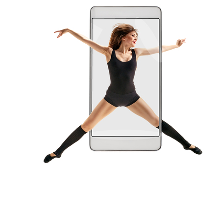 Photo of young beautiful modern female dancer jumping, concept virtual reality of the smartphone. going out of the device 스톡 콘텐츠 - 124967196