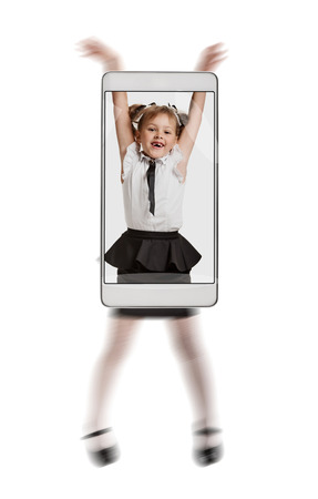 Photo of happy smiling schoolgirl having fun and jumping. conceptual image with a smartphone, demonstration of device capabilities