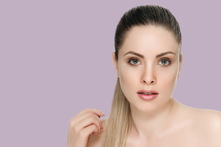 Beautiful face of a woman with clean skin - on background thistle shade violet Stock Photo - 124967199